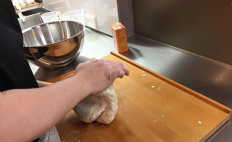 Hands at work kneading dough on bulthaup chopping board.