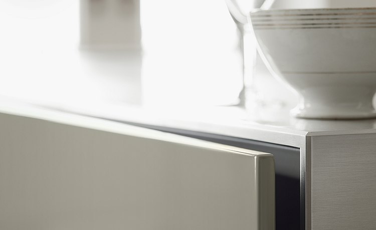 Close-up: combination of a brushed stainless steel surface with light-gray lacquer front panels