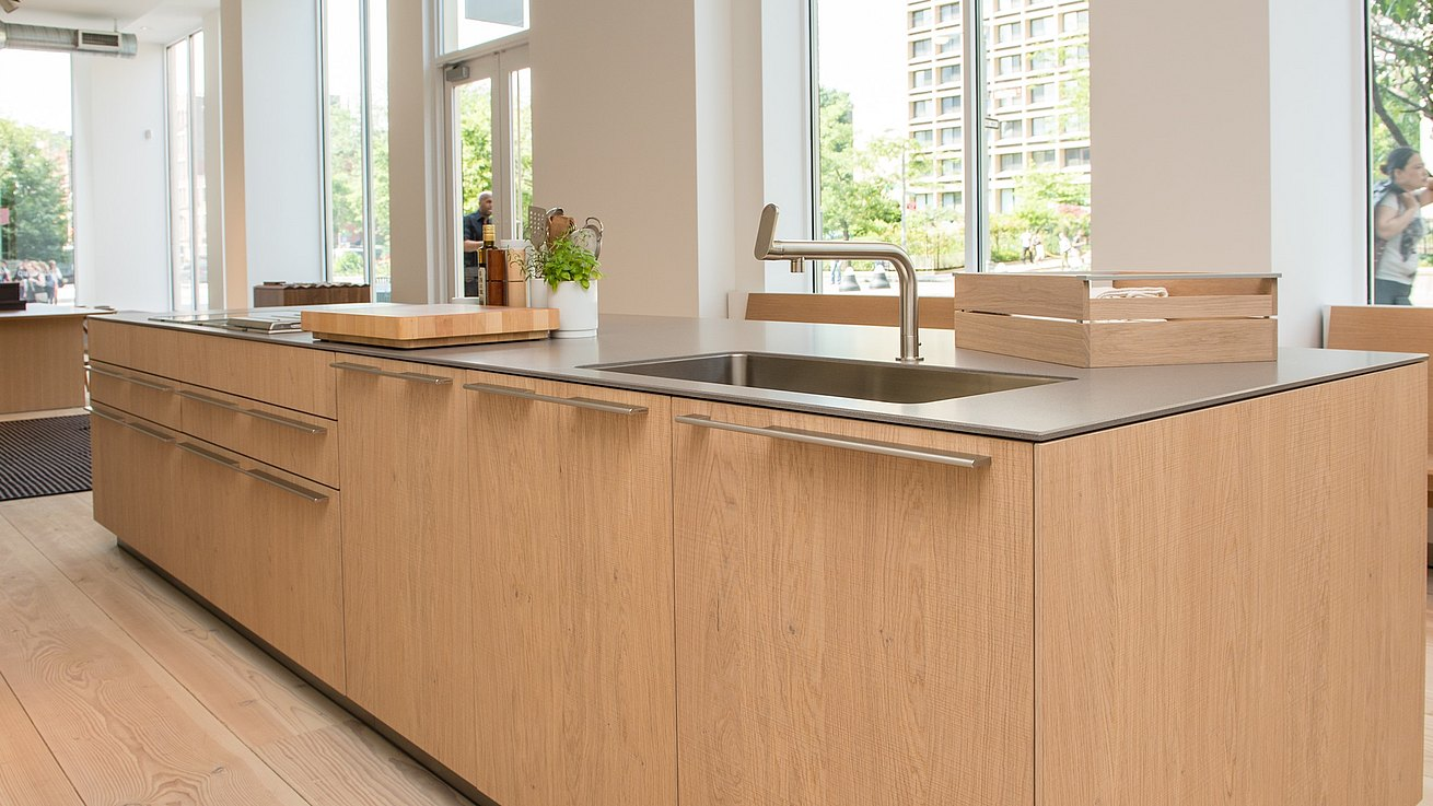 b3 island in vertical solid walnut and stainless steel mono block with hanging kitchen in grey anodized aluminum on wall panel system in natural aluminum.