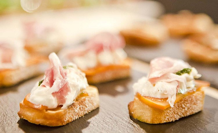 Detail of canape with prosciutto and burrata cheese.