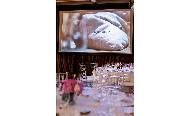 Detail of tables set with pink and white flowers and shimmering glassware with bulthaup Milan 2018 video image still of bulthaup branded cotton sack.
