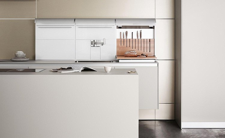Floor-standing, white kitchen island as a connecting element between the living space and multi-functional wall