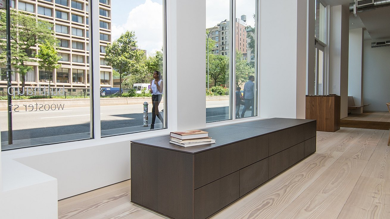 View from inside showroom of passersby on the street and featuring low b3 cabinet in smoked oak.