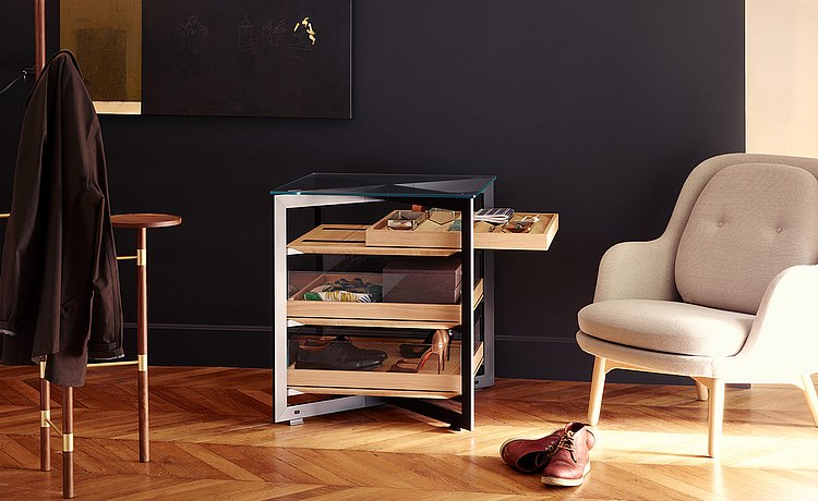 b Solitaire glass, 70 cm-long, with three pull-out wood trays as a storage place for personal items