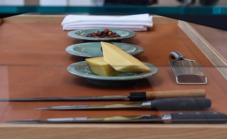 Detail of pull out tray with leather inlay of b Solitaire Glass showing plates prepared with cheese and truffle and special chef knives.