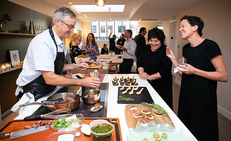 Chef and guests enjoy conversation as food is prepared