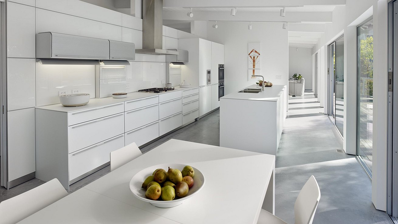 b3 kitchen in alpine white in a residence with lots of sunlight coming through large windows that open out to a deck.