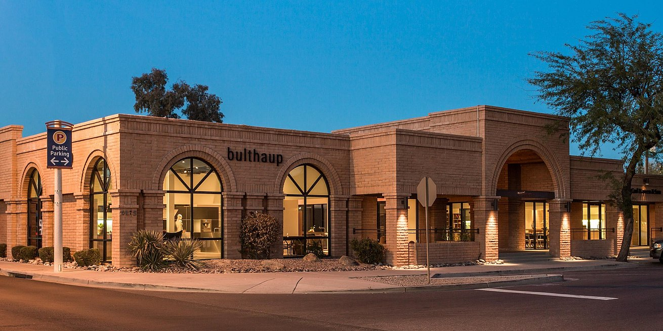 Exterior of bulthaup Scottsdale at dusk showing brick facade and arched windows with glimpses of the showroom displays.