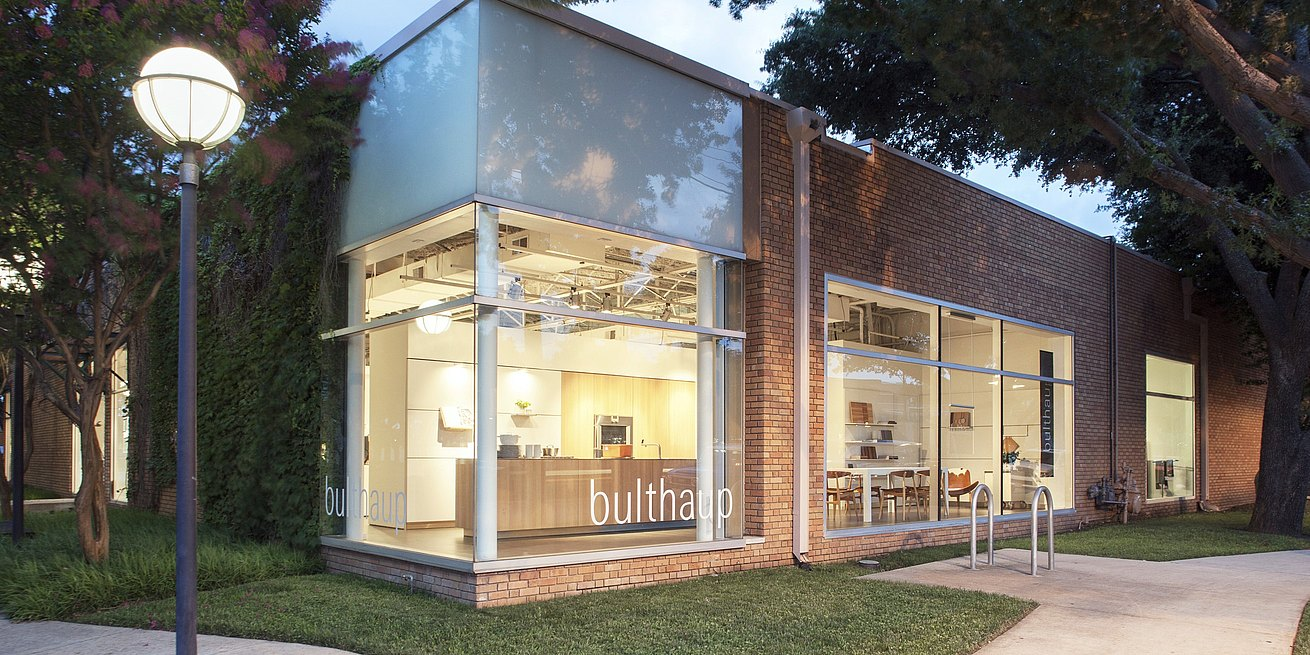 View of exterior of bulthaup Dallas showroom at dusk with b3 display kitchen glowing warm and welcoming.