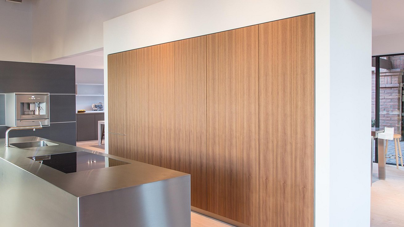 Detail of stainless steel monobloc with tall cabinets in walnut veneer.
