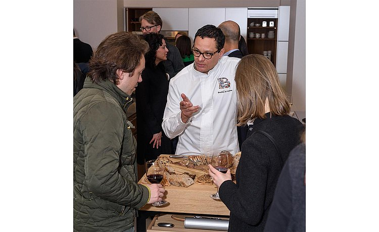 Chef Dani of Bouley at Home at b Solitaire Oak talking with guests over a selection of cut breads.