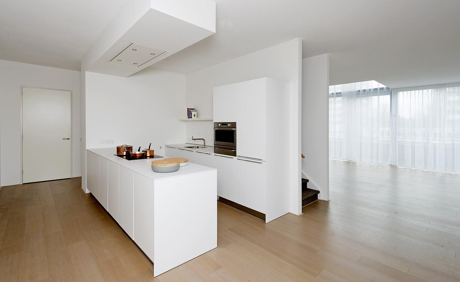 The white b3 with wall line and island as a centerpiece of the open-plan living space