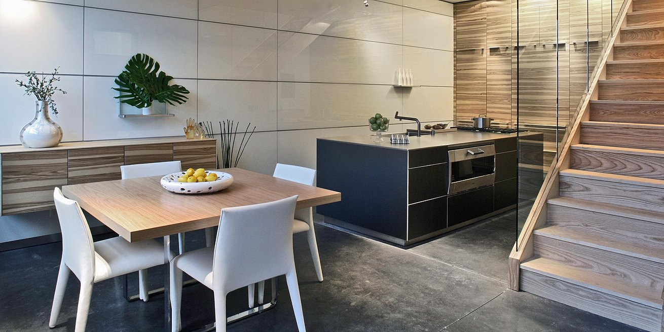 b3 kitchen in walnut, dark grey anodized aluminum and stainless steel in a room with a bulthaup white glass wall panel system, dining table, chairs and a stairwell.