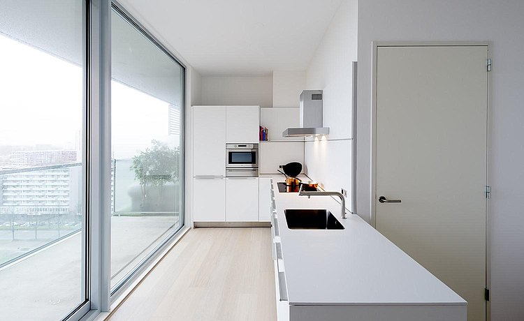 Corresponding to the straight and angular style of construction: the white b3 kitchen continues via the wall to the island
