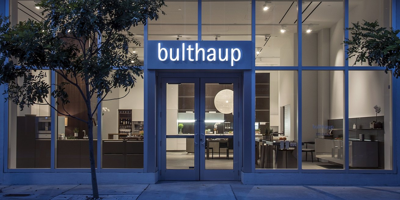 Exterior view of buthaup Miami showroom at night with b3 and b2 kitchen displays gently lit with minimal light.